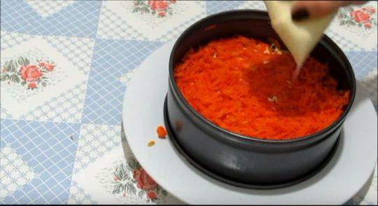 Следом за луком выкладываем тертую вареную морковь