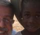 Pe. Henrique sorri com criança moçambicana