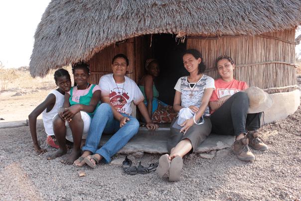Missionários em numa aldeia de Moçambique na entrada de uma casinha de palha