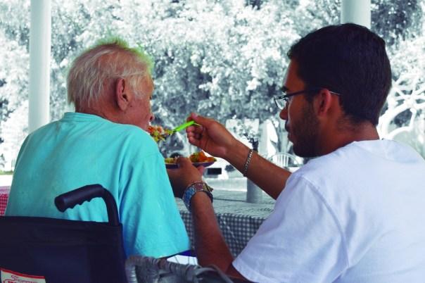 Missionário alimenta idoso.
