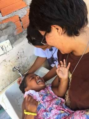 Missionária lava os cabelos de criança da comunidade de Marília