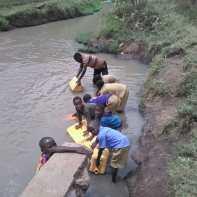 Crianças vão coletam água em rio barrento. Saneamento básico precário
