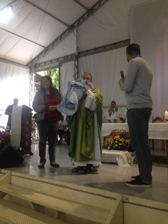 Padre João Henrique apresenta à assembleia um recém nascido.