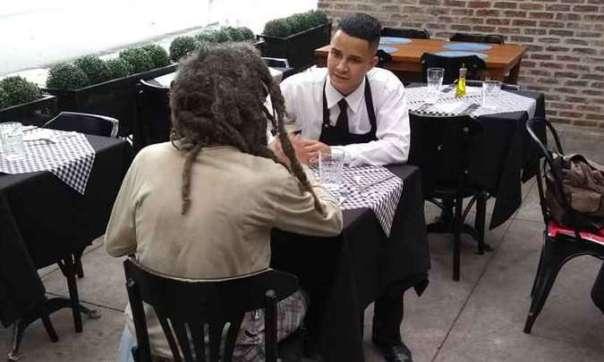 Garçon do Benvindo conversa com homem em situação de rua.