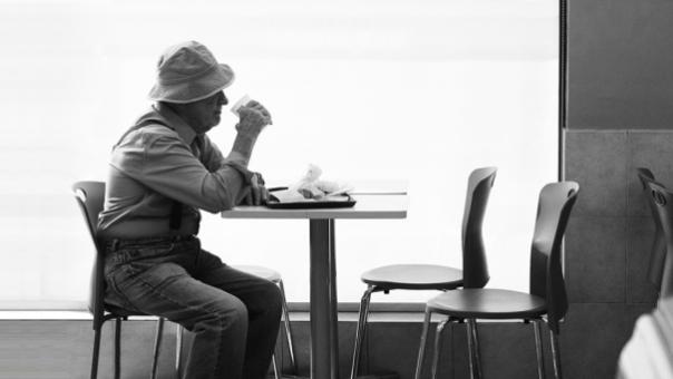 Idoso num café sozinho