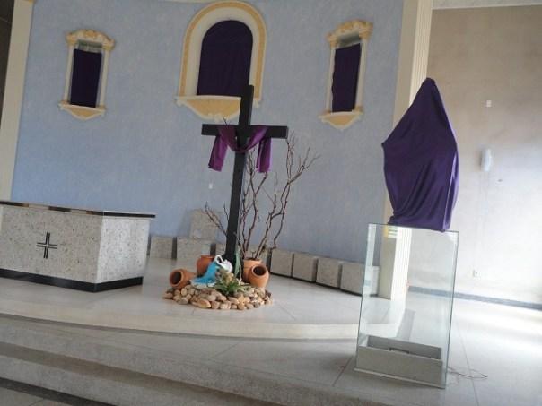 Imagens cobertas com pano roxo em igreja.