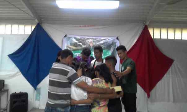 Jovens se abraçam durante dinâmica de oração.