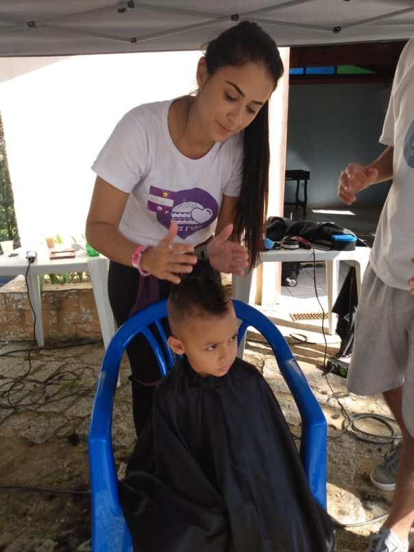 Voluntária realiza corte de cabelo em criança