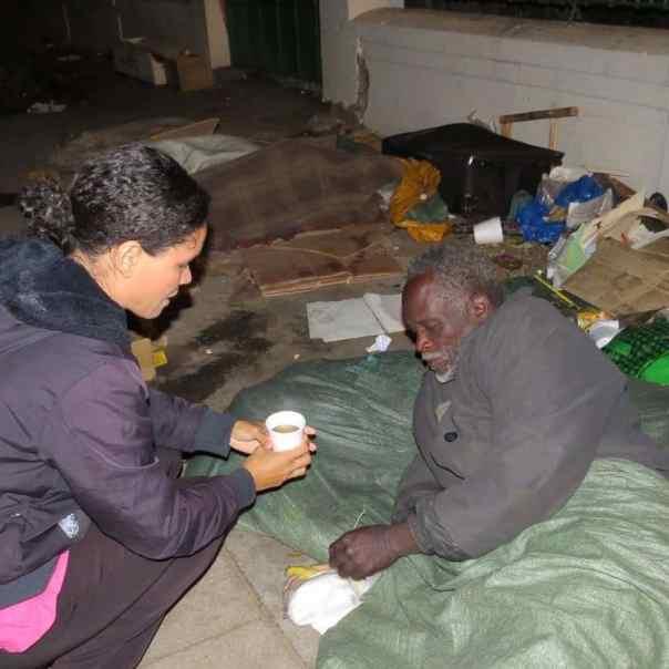 Missionária entrega café a morador de rua em Moçambique.