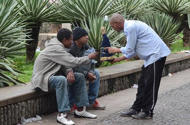 Moradores de rua interagem com imagem de Nossa Senhora Aparecida.