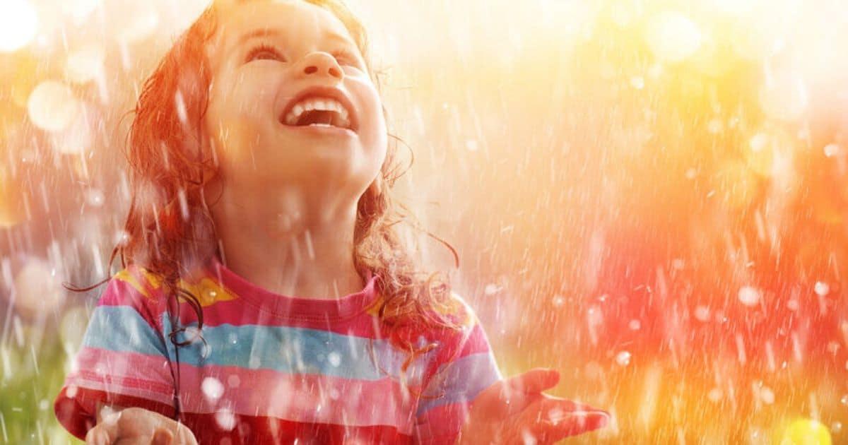 Criança sorri sob a chuva
