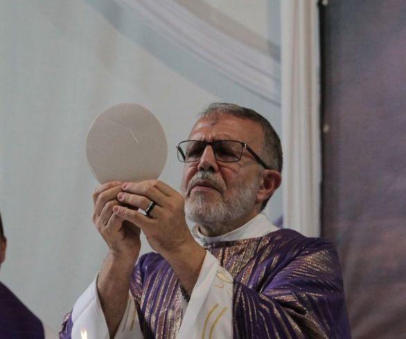Padre João Henrique consagra a hóstia durante a missa