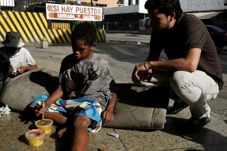 Criança venezuelana recebe alimento de voluntário