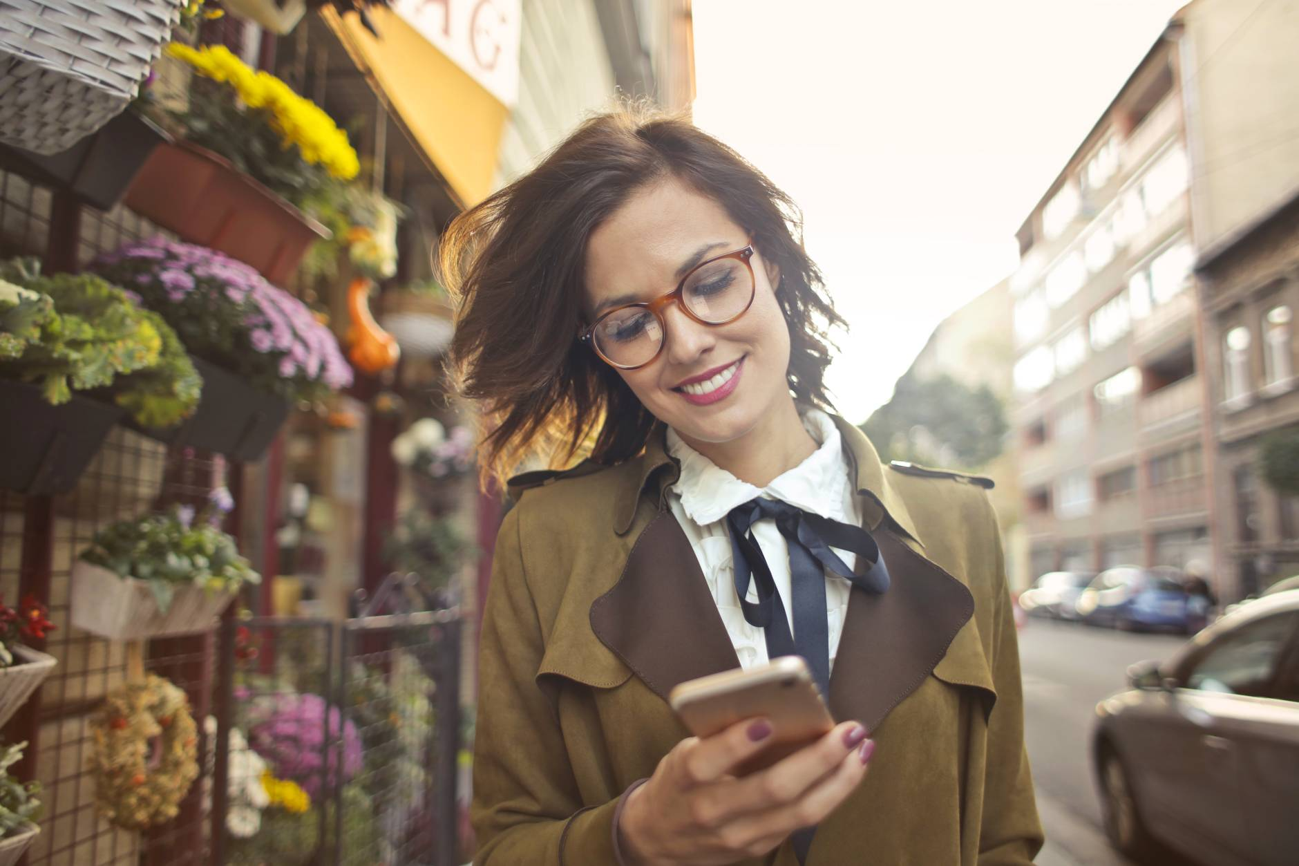 woman beside flower shop using smartphone