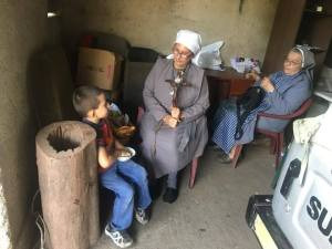 La Hna María Carlota y la Hna. Paula Hidalgo  fundadora de la fraternidad misionera del Fiat de Maria compartiendo con un niño de la escuela
