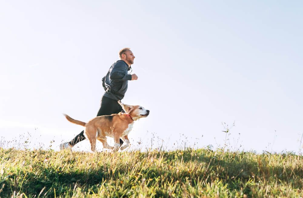Hombre corriendo con perro