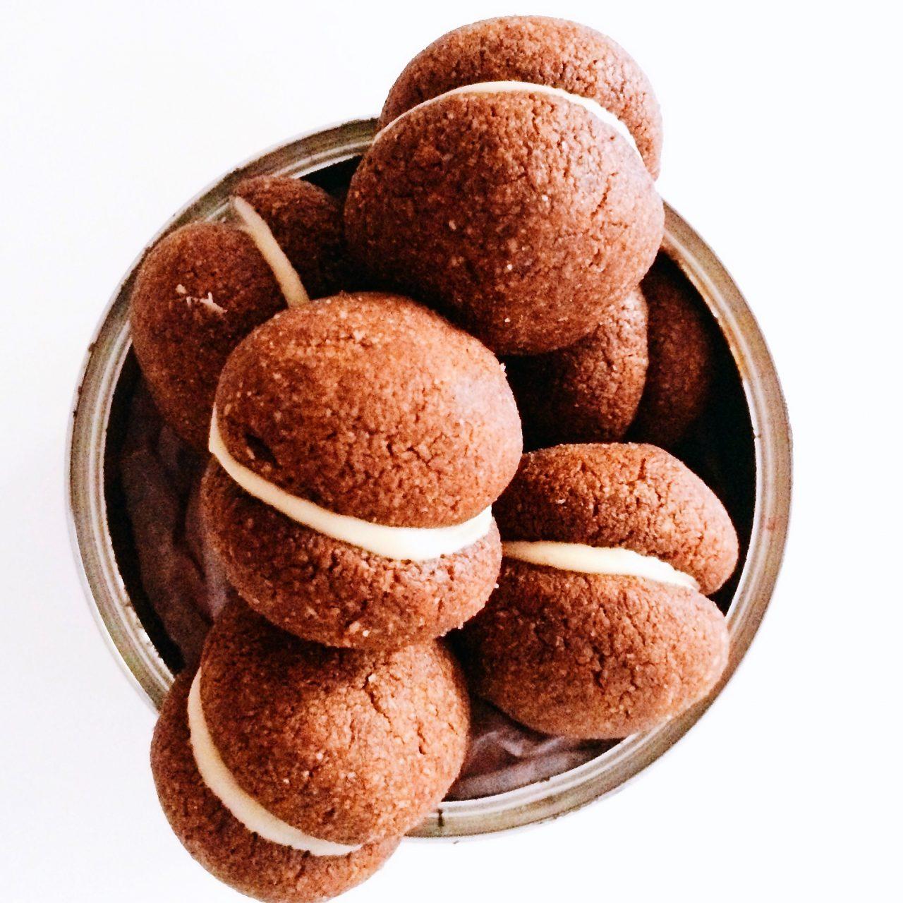 Baci di dama al cacao amaro con crema di mandorle dolci