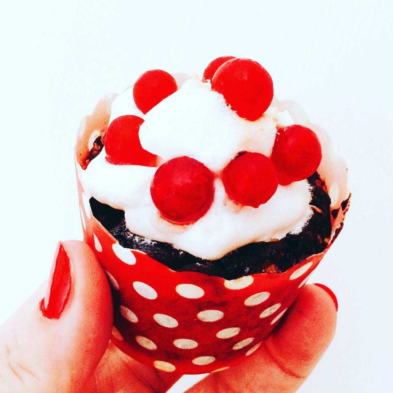 muffin al cioccolato, meringa e ribes in mano