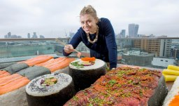 EDITORIAL USE ONLY Hannah Warmington interacts with the worldÕs biggest bento box, which has been commissioned by Groupon to celebrate the capitalÕs love of sushi, London. PRESS ASSOCIATION Photo. Issue date: Wednesday September 21, 2016. Research by Groupon found that sushi is a favourite dish of residents in the capital, and tops the list for the City of London. The platter, which comprises of 350 kilos of rice and 6 sides of salmon, took 4 people, 4 days to complete. Photo credit should read: Anthony Upton/PA Wire