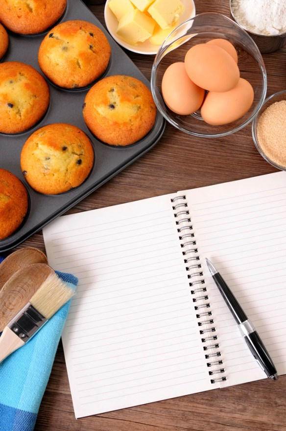 Fresh muffins with blank notebook