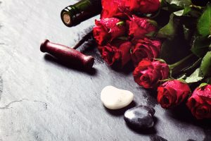 Valentine image with red roses, heart and wine at black stone background.