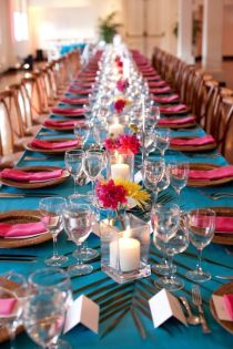 Coral and torquoise table setting with florals and palm leaves