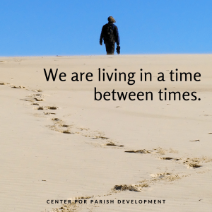 """A figure walks away in the distance on a background of blue sky.  The desert sand below has footsteps and the text """"We are living in a time between times."""""""