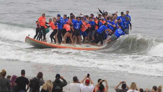 world's largest surfboard ridden by the most number of people ever