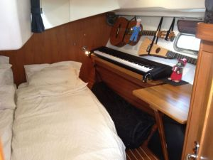 37. Joyful - Anne's side of aft stateroom with 88 key piano, classical & accustic guitars, & art desk.