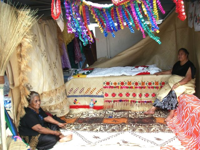 102. This family sits next to their woven mats, tapa cloth, and other traditional Tongan utilitarian crafts, as they patiently wait for the King and Queen and the show's judges to stroll by