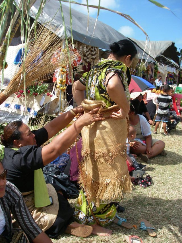 104. This Tongan woman helped her friend adjust the sash on the traditional woven wrap worn to show loyalty to the crown