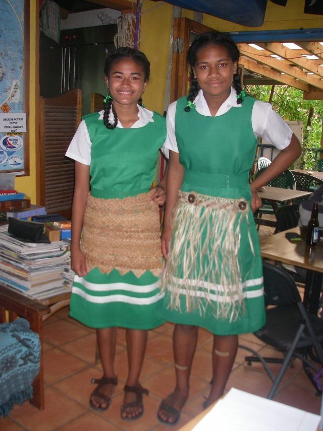 32. Two beautiful Tongan school girls wear over their school uniforms two styles of traditional garments to show homage to the monarchy of Tonga