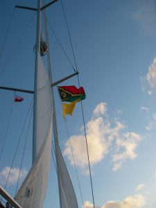 56. Joyful is reefed down for the evening at sea in brusk winds. Her Vanuatu courtesy flag flies above the yellow Q flag which asks for requesting free pratique, and the MaiKai Yacht Club burgee flies on the port flag halyard