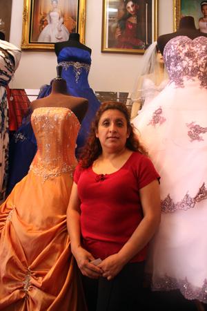 Gloria Martinez poses in front of dresses (photo by Rigoberto Hernandez)
