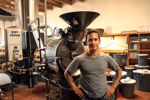 Four Barrel owner Jeremy Tooker stands in front of his coffee shop's roaster.