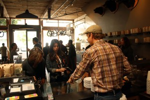 A Four Barrel employee attends to a pair of waiting customers.