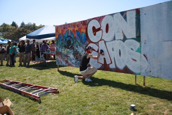 """George Anzaldo spray paints on the community wall. """"I chose to write 'con safos' because it means 'with respect' and we're all out here to respect Chicano rights"""" he said."""