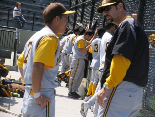 Senior Edgar Linares (left) and assistant coach Mark Probst (right) discuss about a play in the dugout.