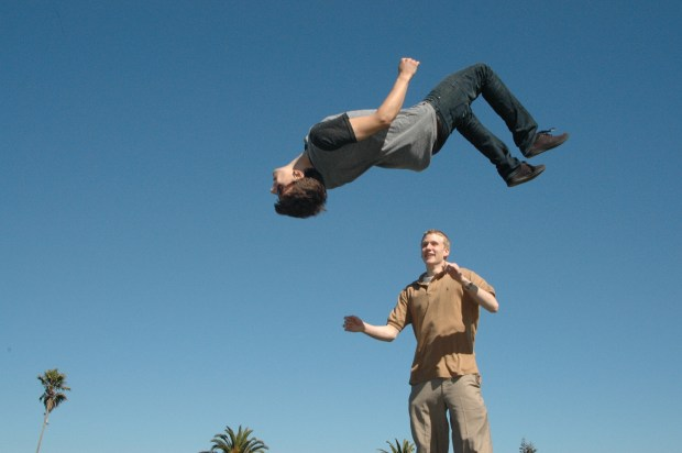 Image shows a man doing a back flip on a trampoline