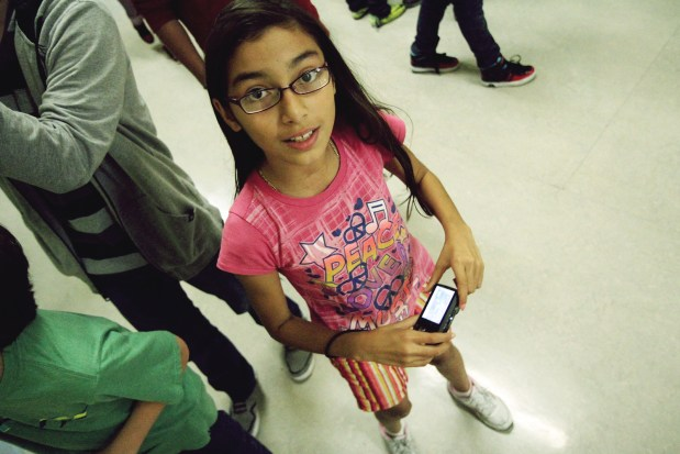 """Marilyn Navarrete, 6th grade student at Buena Vista Horace Mann, taking pictures during Mission Local's """"Reporting in the Mission"""" class."""