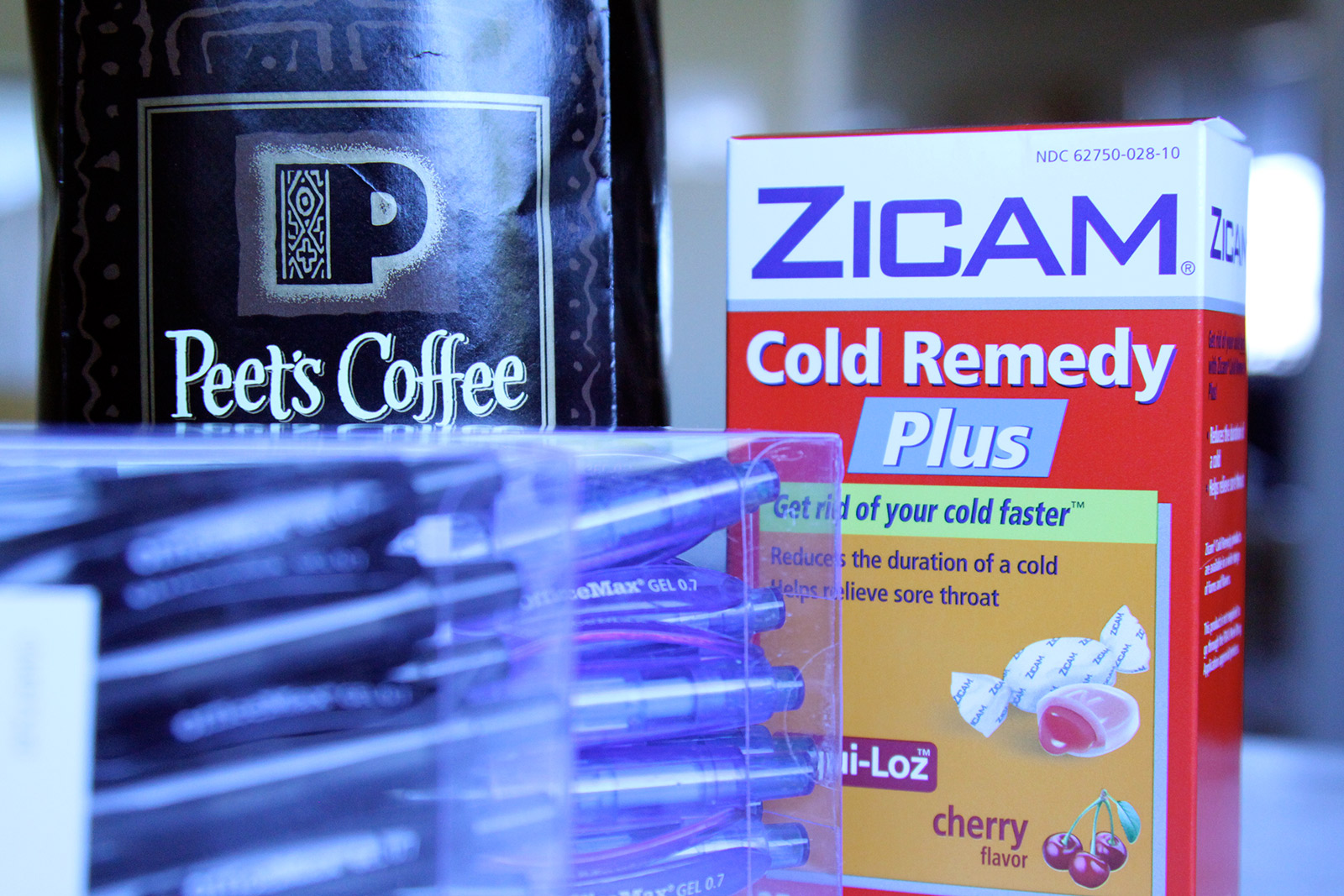 Image shows a bag of coffee, cold medicine, and pens