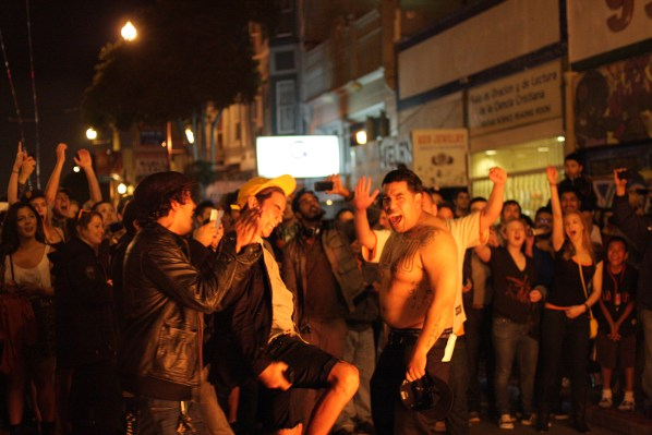 A man takes off his shirt and throws it in the fire as he celebrates with other fans. Photo by Rigoberto Hernandez