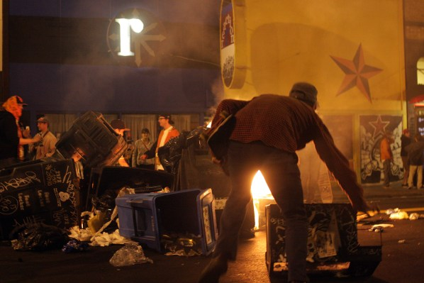 A rioter adds fuel to a fire on 18th and Mission streets on Sunday. Photo by Rigoberto Hernandez