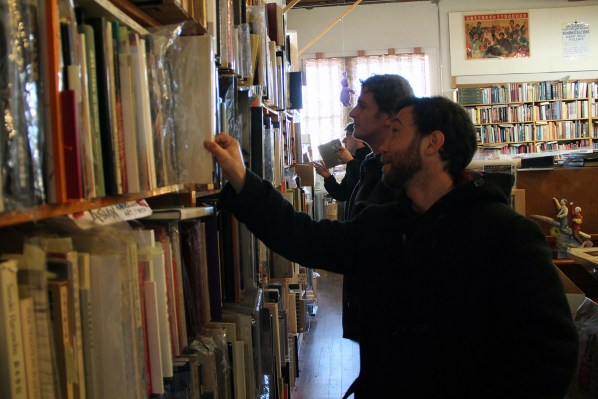 Three young men browse the store's art book collection.