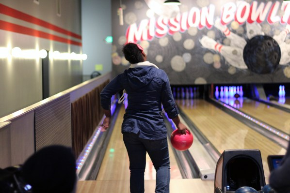 A teenager thinks about her shot before bowling.