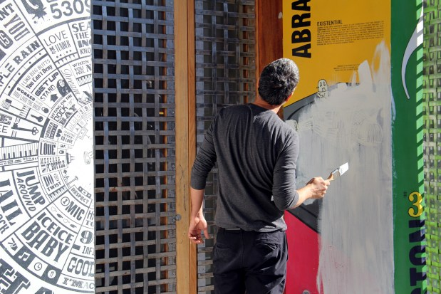 A man paints a building on Mission Street.