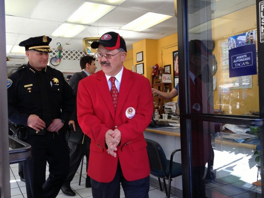 Ed Lee and Greg Suhr walking out of a Mission Street business.