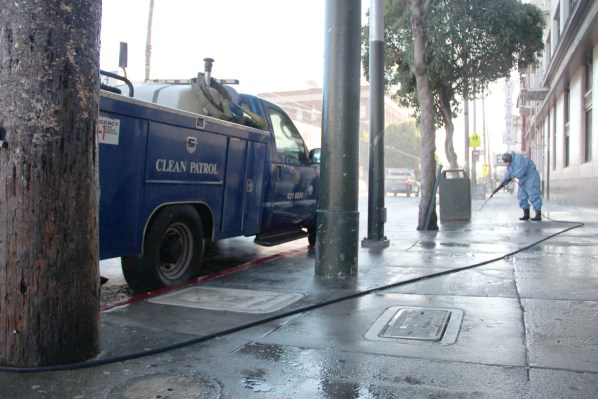 A city worker with the Department of Public Works' Clean Patrol powerwashes along 16th at Mission Street.