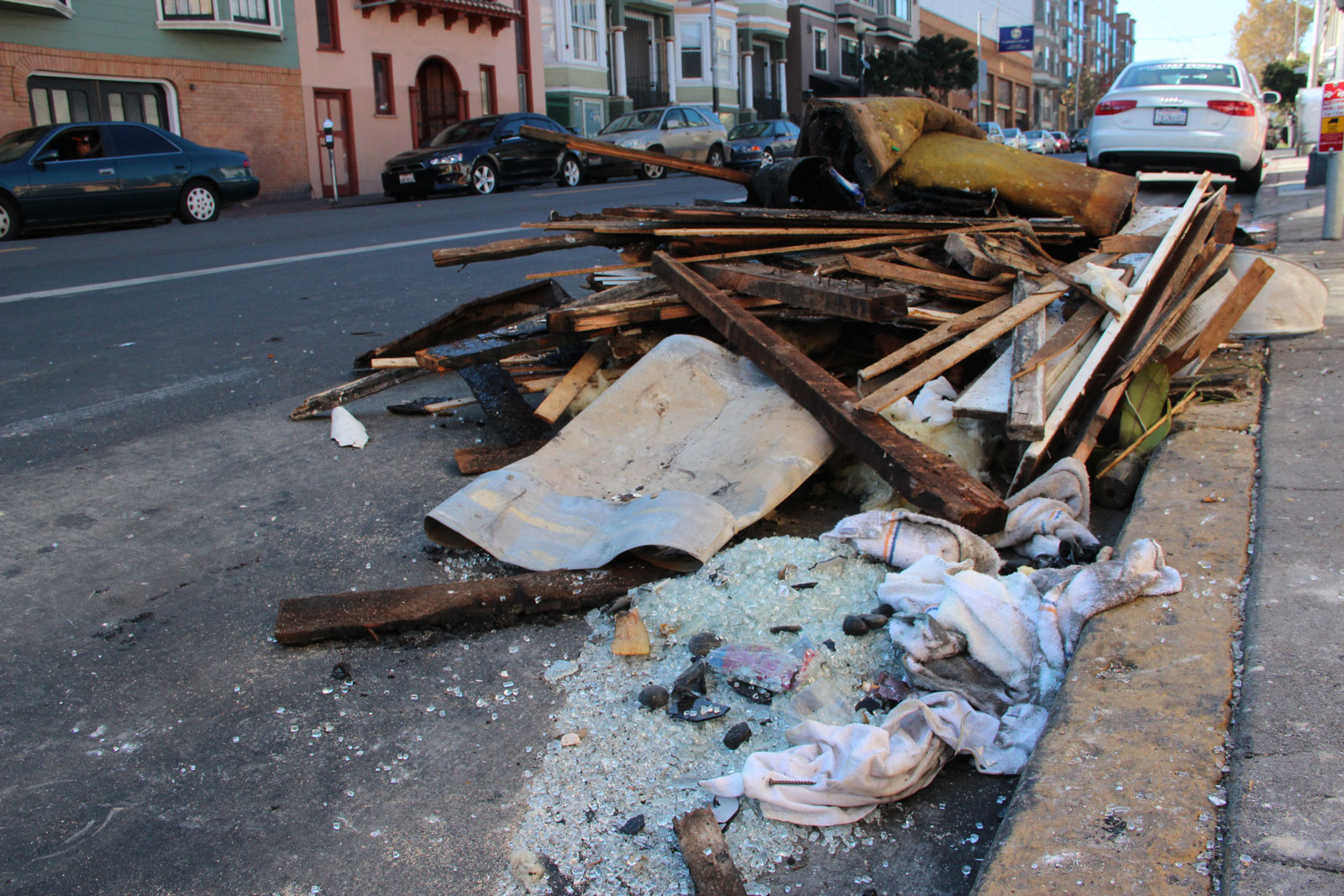 Burnt wood planks and broken glass were stacked on the curb in front of Maverick Saturday. Photo by Andy Mannix.