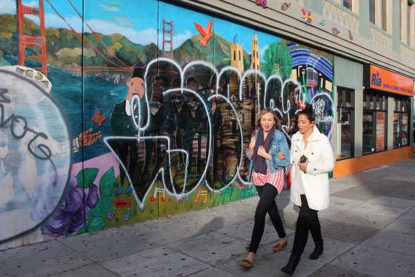 Pedestrians walk past the defaced mural on 21st Street at Mission.